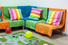 有一个明亮的沙发、玩具和气球的儿童居室在地板上 库存图片