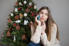 有一个智能手机的女孩在圣诞树附近 免版税库存图片