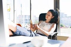 有一个智能手机的女实业家在她的办公室 免版税库存照片