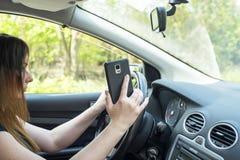 有一个智能手机的妇女在汽车 图库摄影
