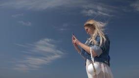 有一个智能手机的年轻白肤金发的妇女在手中反对天空蔚蓝慢动作底视图 股票录像