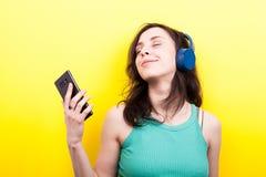 有一个智能手机的微笑的女孩在手上听到音乐的 库存图片
