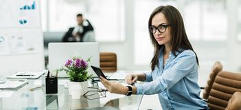 有一个智能手机的成功的女商人在工作场所 库存图片