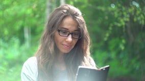 有一个智能手机的美丽的少妇在夏天公园 股票视频