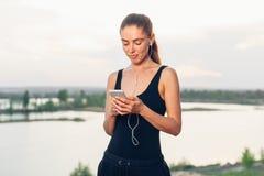 有一个智能手机的训练健身的女孩在自然背景,享受体育,锻炼 库存照片