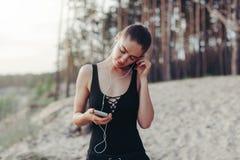 有一个智能手机的训练健身的女孩在自然背景,享受体育,锻炼 免版税库存照片