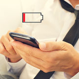 有一个智能手机的年轻人有低电池的 免版税库存照片
