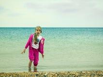 有一个有趣的表示的女孩在他的在冷的海水的面孔 免版税库存图片