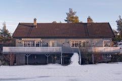 有一个木甲板的长的灰色楼层房子 免版税库存图片