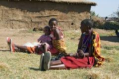 有一个未认出的婴孩的Maasai妇女在泥被修造的小屋前面休息 库存图片