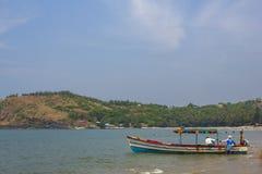 有一个机盖的大色的游船在含沙岸附近衬托 免版税库存照片