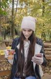 有一个杯子的女孩热的饮料打录影电话给朋友 库存图片