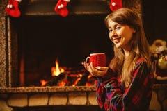 有一个杯子的妇女由壁炉 年轻有吸引力的妇女sittin 库存照片