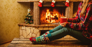 有一个杯子的妇女由壁炉 年轻有吸引力的妇女sittin 免版税库存图片