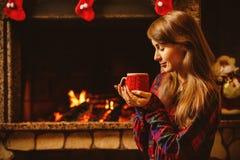有一个杯子的妇女由壁炉 年轻有吸引力的妇女sittin 免版税库存照片