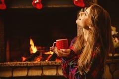 有一个杯子的妇女由壁炉 年轻有吸引力的妇女sittin 图库摄影