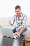 有一个杯子的微笑的人使用膝上型计算机 免版税库存照片