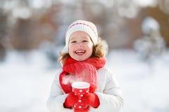 有一个杯子的愉快的儿童女孩在冬天步行的热的茶 免版税库存照片