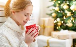 有一个杯子的愉快的妇女在圣诞树附近的茶 免版税图库摄影