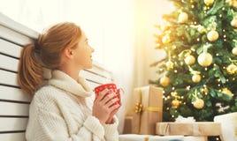 有一个杯子的愉快的妇女在圣诞树附近的茶 免版税库存照片