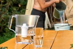 有一个杯子的滤水器有赤裸上身的从井的较少人倾吐的水 免版税库存图片