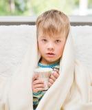 有一个杯子的病的哀伤的男孩在他的手上坐在毯子包裹的床 图库摄影