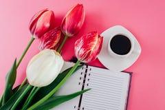 有一个杯子的笔记本esspresso咖啡和新鲜的郁金香在桃红色背景 免版税库存图片