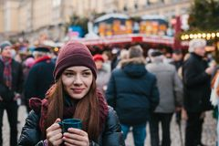 有一个杯子的美丽的女孩热的饮料在圣诞节市场上在德累斯顿 庆祝圣诞节在欧洲 库存照片