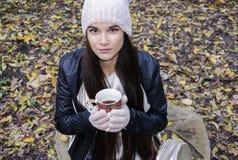 有一个杯子的美丽的女孩热的饮料 库存照片