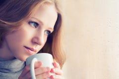 有一个杯子的美丽的梦想的女孩在视窗的热咖啡 库存照片