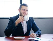 有一个杯子的英俊的正面商人在办公室背景的热的茶 早晨咖啡概念 复制空间 库存照片