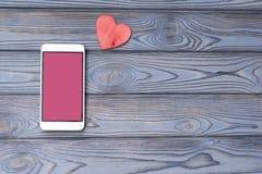 有一个桃红色屏幕的智能手机,在木背景的心脏形状 免版税库存图片