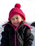 有一个桃红色帽子的愉快的白肤金发的女孩 库存图片
