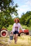 有一个桶的农夫夫人在果树园 库存照片