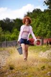 有一个桶的农夫夫人在果树园 免版税图库摄影
