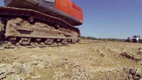 有一个桶的拖拉机在去通过在地面上的照相机的轨道 股票录像
