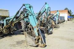 有一个桶的拖拉机开掘的土壤的 推土机和平地机 库存图片