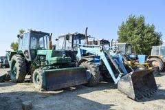 有一个桶的拖拉机开掘的土壤的 推土机和平地机 免版税库存照片