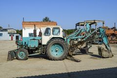 有一个桶的拖拉机开掘的土壤的 推土机和平地机 库存照片