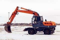 有一个桶身分的挖掘机在一个多雪的领域 免版税图库摄影