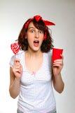 有一个棒棒糖和一个杯子的惊奇的女孩在灰色返回 免版税库存图片