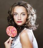 有一个棒棒糖的卷曲女孩在她的手上 库存图片