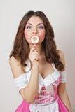 有一个棒棒糖的可爱的女孩在白色隔绝的她的手和桃红色礼服。使用与棒棒糖的美丽的长的头发浅黑肤色的男人 免版税库存照片