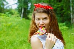 有一个棒棒糖的女孩在树 库存图片
