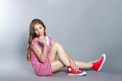 有一个棒棒糖的美丽的女孩在她的手上在灰色背景摆在 一件礼服的女孩在与白色条纹的红色 时尚口味 库存照片