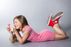 有一个棒棒糖的美丽的女孩在她的手上在灰色背景摆在 一件礼服的女孩在与白色条纹的红色 时尚口味 免版税库存图片