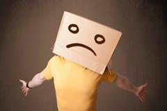 有一个棕色纸板箱的年轻人在他的有哀伤的面孔的头 库存图片