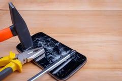 有一个残破的屏幕的一个智能手机谎言螺丝刀,钳子和锤子 免版税库存图片