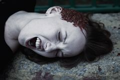有一个残破的头的少妇在血液 库存图片