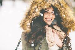 有一个毛皮敞篷的少妇在雪的公园 免版税图库摄影